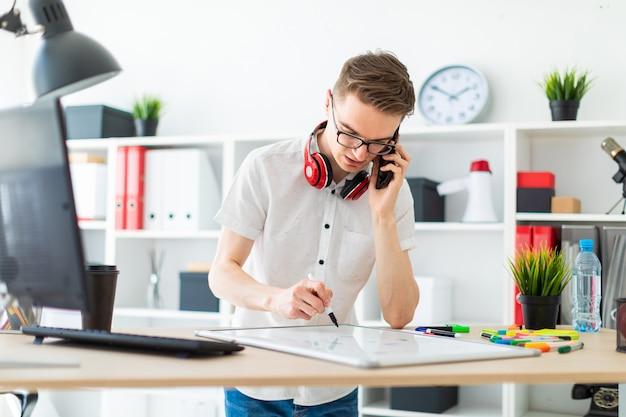 Um jovem de óculos fica perto de uma mesa de computador e está falando ao telefone. diante dele está um quadro magnético e marcadores. no pescoço, os fones de ouvido do cara estão pendurados.