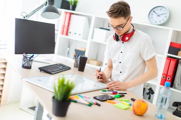 Um jovem de óculos fica perto de uma mesa de computador. um jovem desenha um marcador em um quadro magnético. no pescoço, os fones de ouvido do cara estão pendurados.