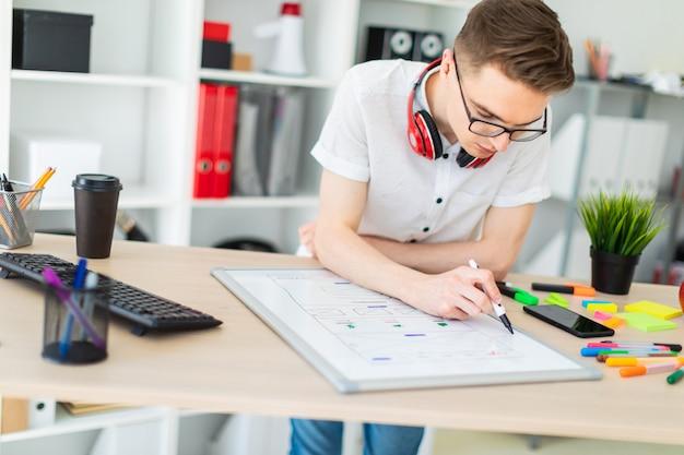 Um jovem de óculos fica perto de uma mesa de computador.