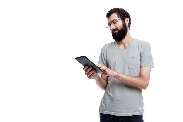 Um jovem de oráculo e com barba e com o apartamento nas mãos olha para a tela. blogging, comunicação online e redes sociais. isolado.