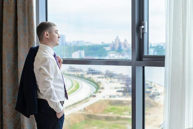 Um jovem de pé na janela