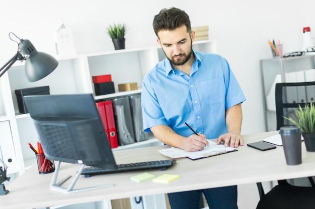 Um jovem de pé no escritório e trabalhando na mesa do computador.