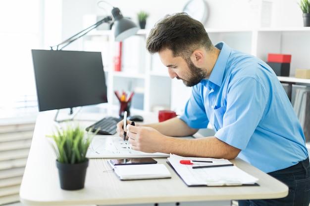 Um jovem de pé no escritório em uma mesa de computador e trabalhando com uma placa magnética.