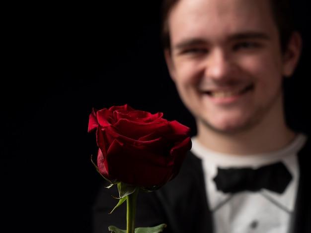 Um jovem de terno preto tem uma rosa vermelha nas mãos e mostra-a no preto