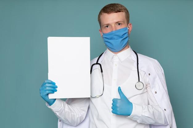 Um jovem de vista frontal em terno médico branco azul luvas e máscara em cima da mesa azul