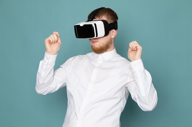 Um jovem de vista frontal jogando vr em camiseta branca no espaço azul