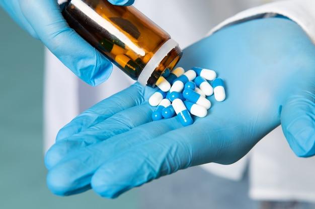 Um jovem de vista frontal na camisa branca e luvas azuis tomando pílulas no espaço azul
