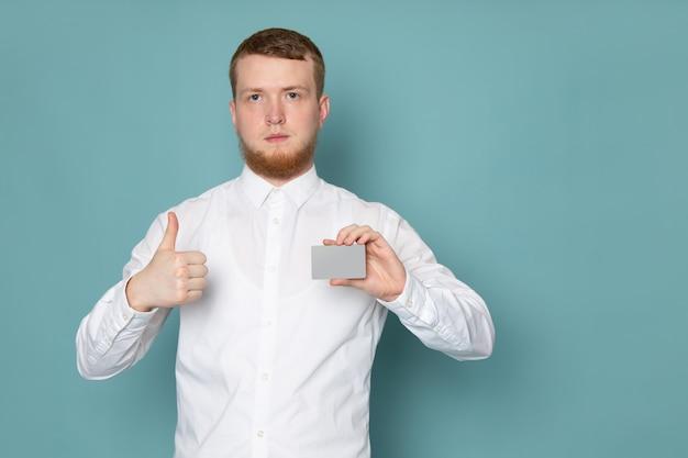 Um jovem de vista frontal na camisa branca, segurando o cartão no espaço azul