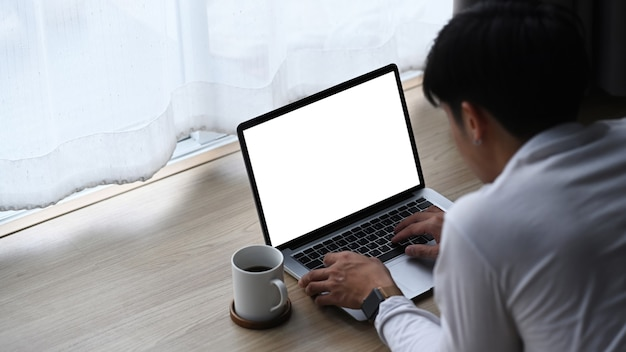Um jovem deitado no chão de madeira e trabalhando no laptop em casa.