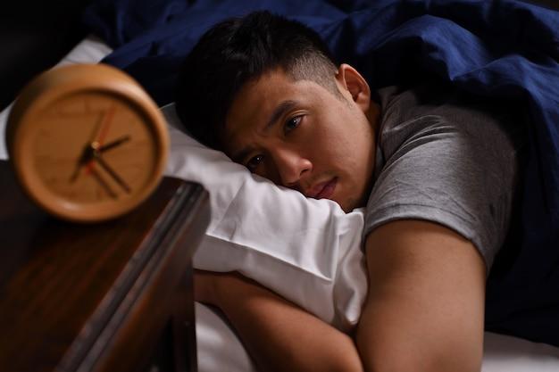 Um jovem deprimido com insônia deitado na cama