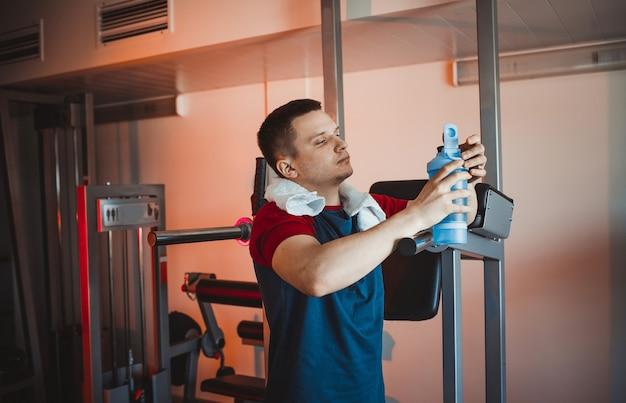 Um jovem descansa após um treino na academia, segurando um shaker na mão. olhar pensativo