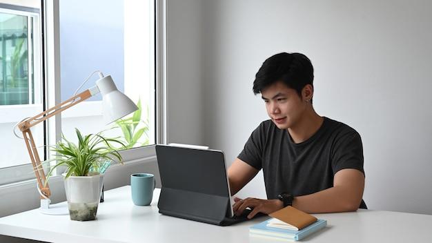 Um jovem designer está trabalhando em um tablet de computador no espaço de trabalho.