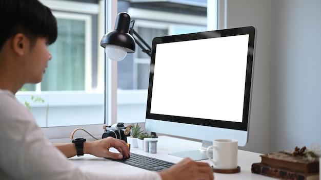 Um jovem designer gráfico sentado em frente ao computador no estúdio gráfico e trabalhando online