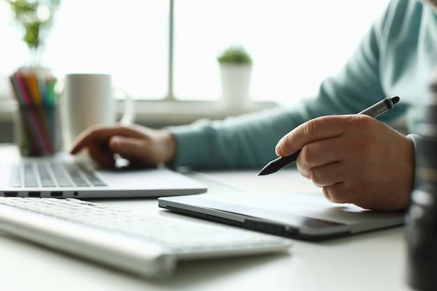 Um jovem designer segura uma caneta de um tablet em sua