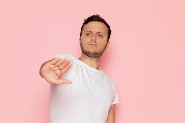 Um jovem do sexo masculino com camiseta branca e uma placa de pare