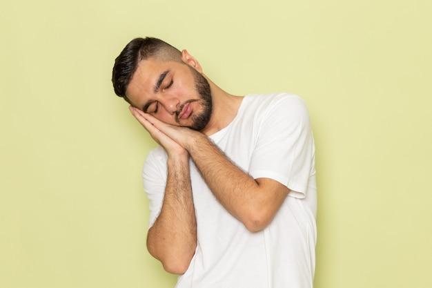 Um jovem do sexo masculino com camiseta branca em pose de dormir