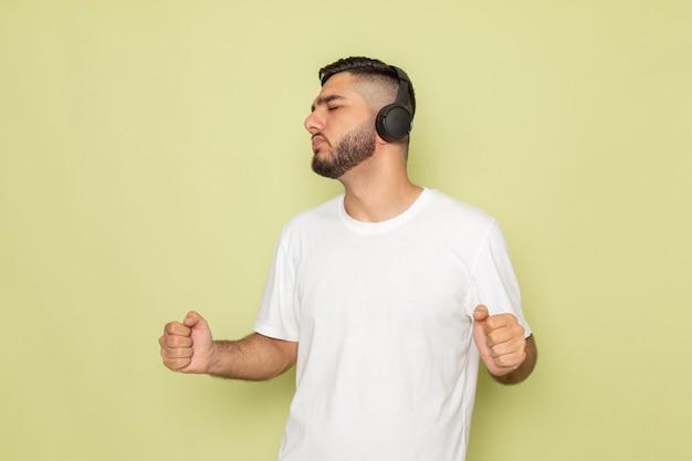 Um jovem do sexo masculino com camiseta branca ouvindo música