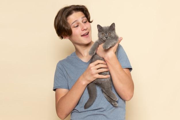 Um jovem do sexo masculino com camiseta cinza segurando um gatinho cinza fofo