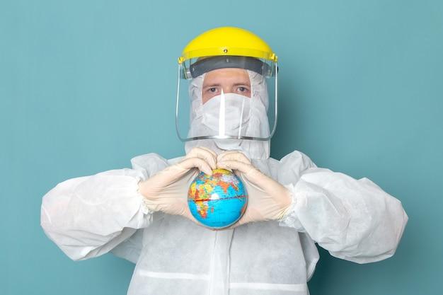 Um jovem do sexo masculino com terno especial branco e capacete especial amarelo segurando o globo na parede azul homem terno perigo cor de equipamento especial