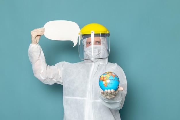 Um jovem do sexo masculino com terno especial branco e capacete especial amarelo segurando um globo e uma placa branca na parede azul homem terno cor especial perigo