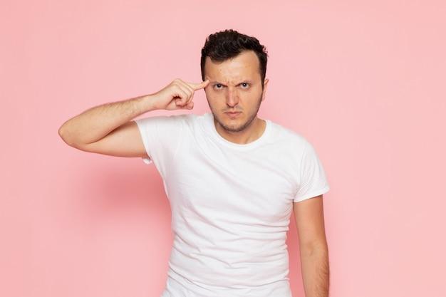 Um jovem do sexo masculino com uma camiseta branca posando com uma expressão de raiva