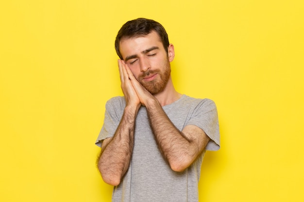 Um jovem do sexo masculino com uma camiseta cinza e uma pose de dormir na parede amarela.