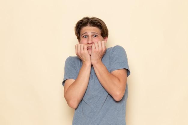 Um jovem do sexo masculino com uma camiseta cinza posando com expressão de medo
