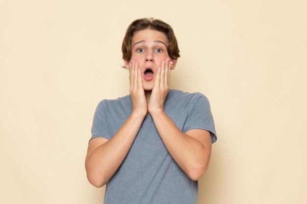 Um jovem do sexo masculino com uma camiseta cinza posando com expressão de surpresa
