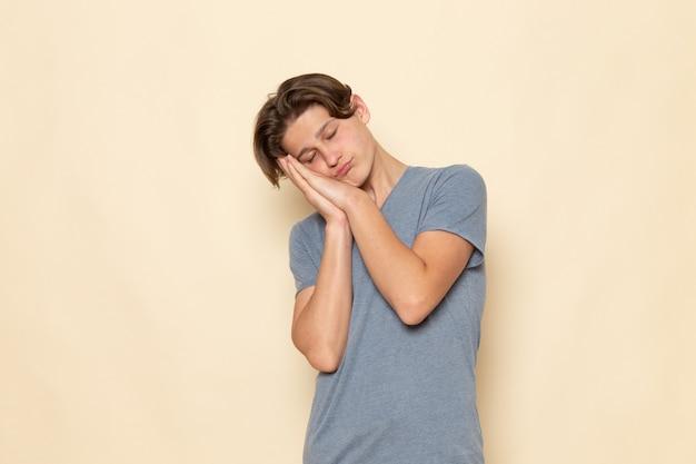 Um jovem do sexo masculino com uma camiseta cinza posando com uma expressão adormecida