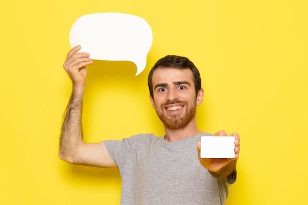 Um jovem do sexo masculino com uma camiseta cinza segurando uma placa branca e um cartão branco no modelo de cor do homem na parede amarela
