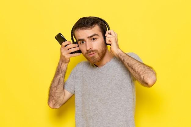 Um jovem do sexo masculino com uma camiseta cinza usando o telefone e ouvindo música na parede amarela.