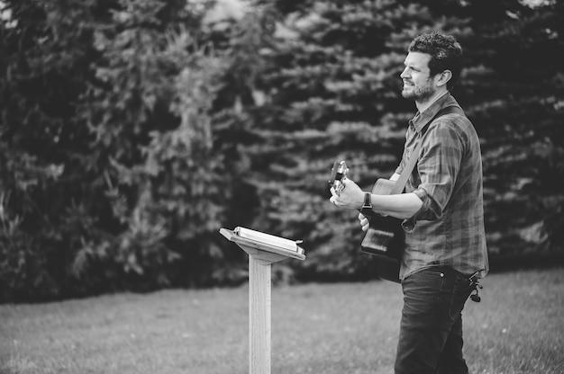 Um jovem do sexo masculino em um parque segurando um violão e tocando uma música do livro de hinos cristãos