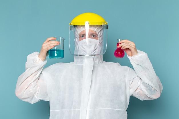 Um jovem do sexo masculino em um terno especial branco e um capacete especial amarelo segurando soluções na parede azul.