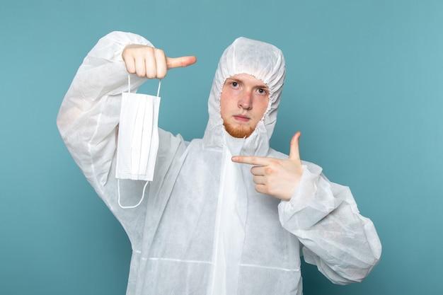Um jovem do sexo masculino em um terno especial branco mostrando uma máscara protetora estéril na parede azul.