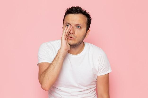 Um jovem do sexo masculino em uma camiseta branca sussurrando na mesa rosa homem cor de emoção pose