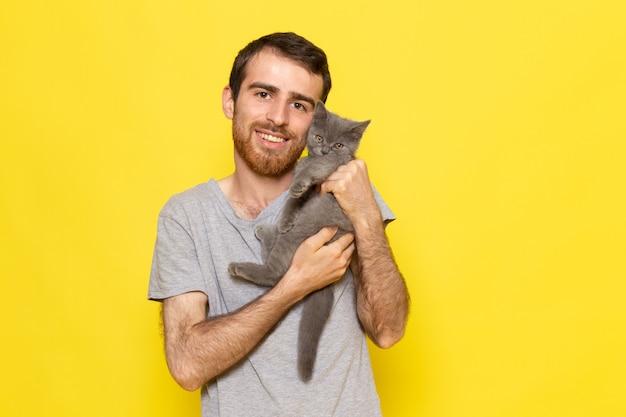 Um jovem do sexo masculino em uma camiseta cinza segurando um lindo gatinho cinza na parede amarela homem expressão emoção cor modelo