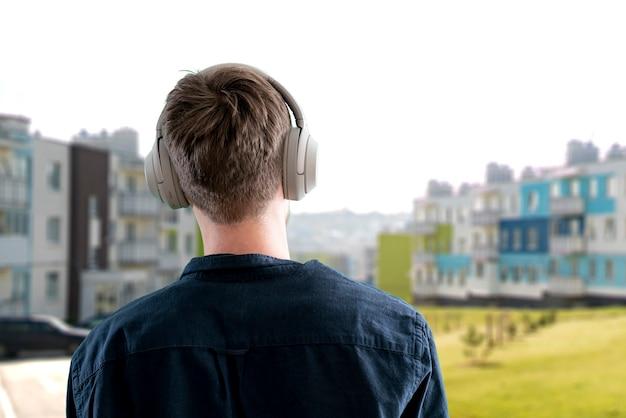 Um jovem do sexo masculino ouve fones de ouvido, aproveita o áudio, relaxe e relaxe