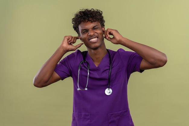 Um jovem e agressivo médico bonito de pele escura com cabelo encaracolado, usando uniforme violeta com estetoscópio segurando as orelhas nas mãos enquanto está em um espaço verde