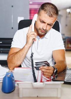 Um jovem e ambicioso negociante do mercado de ações está fechando um negócio por telefone em um escritório cheio de computadores.