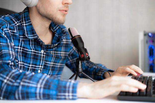 Um jovem e bonito apresentador gravando podcast no estúdio, transmitindo ao vivo