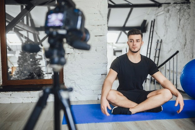 Um jovem e bonito blogueiro de fitness escreve vídeos para seu blog e conta as regras básicas durante um treino, em uma sala estilo loft