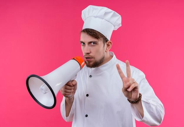 Um jovem e bonito chef barbudo, de uniforme branco, falando através do megafone e mostrando o gesto de dois dedos enquanto olha para uma parede rosa
