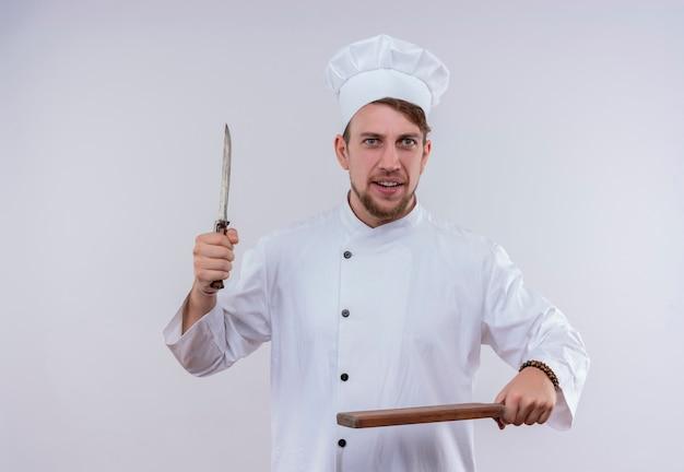 Um jovem e bonito chef barbudo vestindo uniforme de fogão branco e chapéu segurando uma faca e uma tábua de cozinha de madeira enquanto olha para uma parede branca