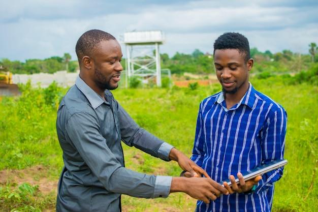 Um jovem e bonito empreiteiro africano explicando ao colega sobre o trabalho que estão prestes a fazer em uma fazenda