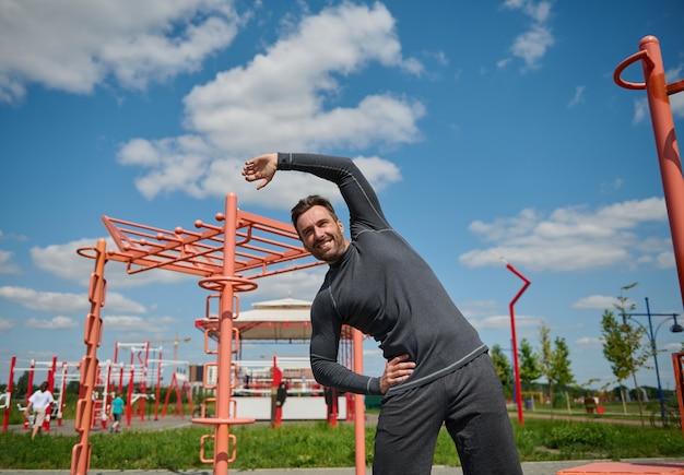 Um jovem e bonito homem caucasiano europeu, de constituição atlética, pratica esportes em um campo de esportes de verão, executa as curvas laterais e estende o braço.