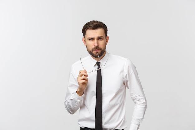 Um jovem e bonito homem milenar caucasiano de óculos e uma camiseta branca isolado em um estúdio cinza, olha para uma cópia em branco