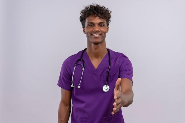 Um jovem e bonito médico de pele escura com cabelo encaracolado e uniforme violeta com estetoscópio estendendo a mão para cumprimentar alguém ou para dizer olá