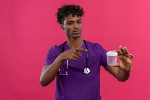 Um jovem e bonito médico de pele escura com cabelo encaracolado, usando uniforme violeta com estetoscópio apontando com o dedo indicador para o frasco de plástico médico