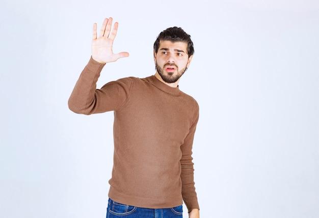 Um jovem e bonito modelo olhando para longe e levantando a mão.