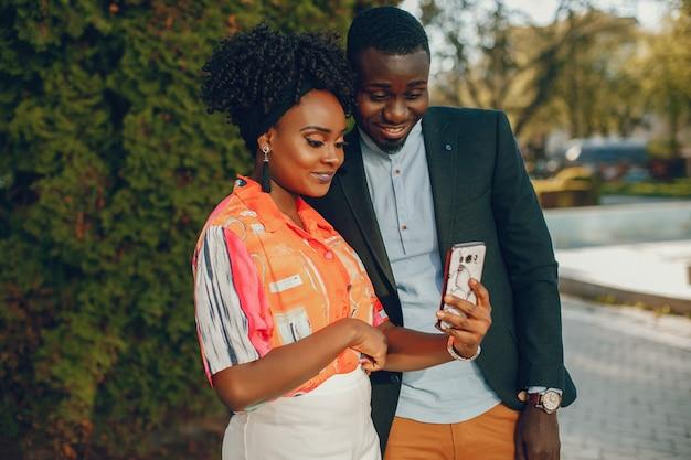 Um jovem e elegante casal de pele escura em pé em uma cidade ensolarada e usar o telefone
